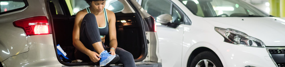 Woman tying shoes sitting inside car