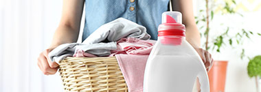 Woman doing laundry with rigid detergent bottle in front