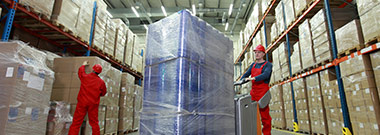 Employee moving a pallet of products wrapped in stretch film