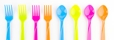 Row of neon colored spoons and forks laid out on a white background