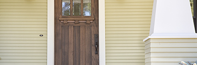 Closed wooden door of a home with yellow siding