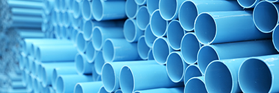 Blue PVC pipes stacked in a construction site