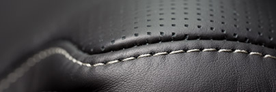 Close up of stitches on a black leather seat