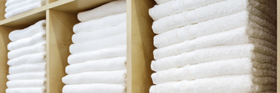White towels folded and stacked on a shelf