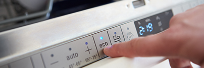 Person setting economy cycle on dishwasher