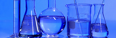 Close up of laboratory flasks containing blue colored liquid