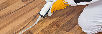 Worker applies silicone sealant to wooden floor