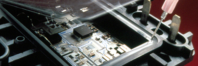 Adhesive in syringe applied to seal of heat sink assembly around electronic circuit board