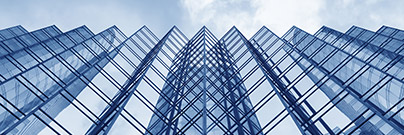 Looking up at the glass facade of a modern office building