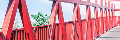 Iron truss footbridge painted in vivid red seen in perspective
