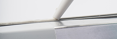 Close up of white assembly adhesives and sealants on a white background