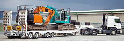 Truck towing hydraulic excavators