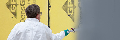 Man spraying AirBarrier system, DefendAir, on a wall outside.