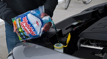 Windshield fluid being poured into engine compartment from PacXpert package
