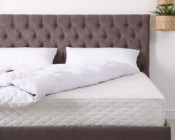 White bed with ruffled sheets
